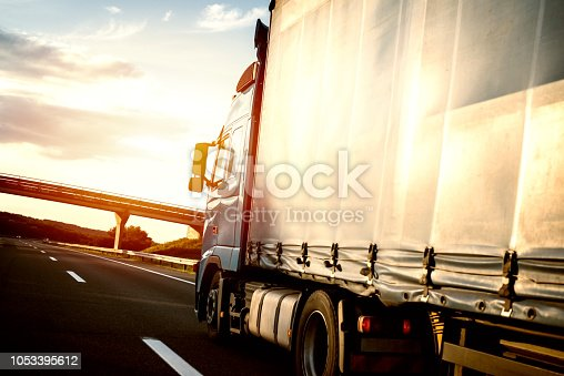 Truck on the road in motion. Long vehicle cruising highway in sunset.