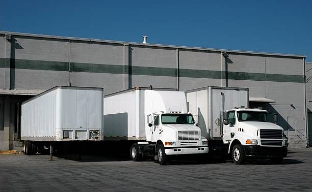 trucks at the loading docks - lorries unloading stock photos and pictures