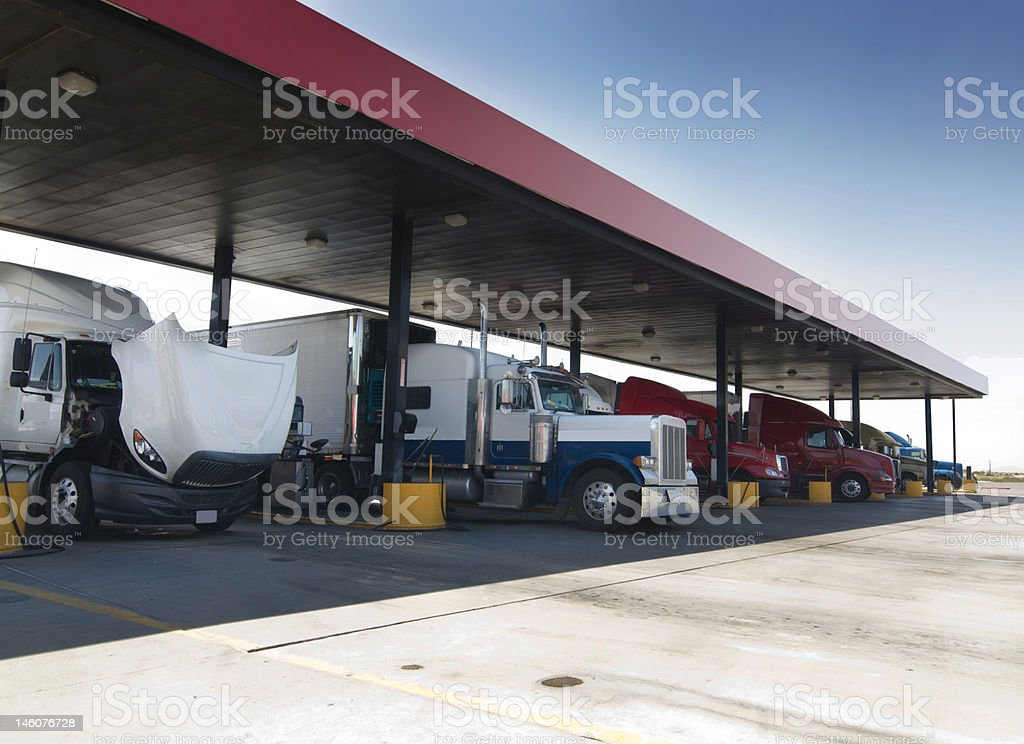 Trucks fueling at gas station just off highway stock photo