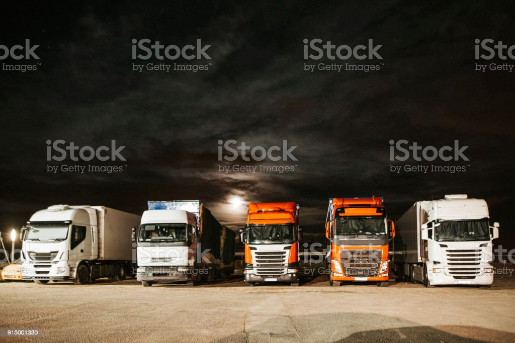 Trucks in a parking lot at night stock photo
