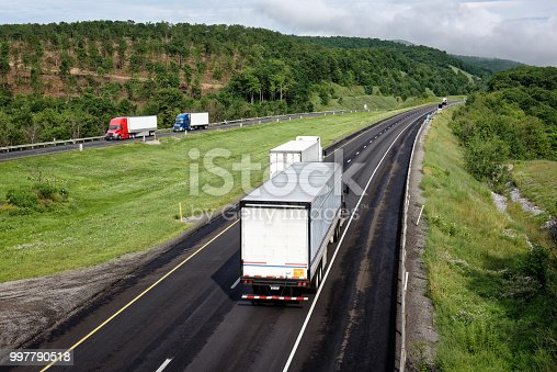 Trucks moving down an interstate highway through the scenic eastern mountains, tractor trailers in transportation and trucking industry hauling freight, some motion blur.