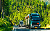 Truck in summer road of Switzerland. Trucker in highway. Lorry doing logistics work. Semi trailer with driver. Big cargo car drive. Freight delivery. Transport export industry. Container with goods