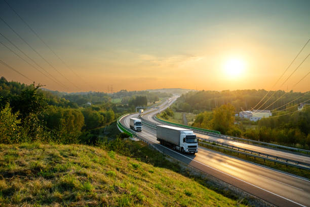 Trucks on the highway winding through forested landscape at sunset - foto stock