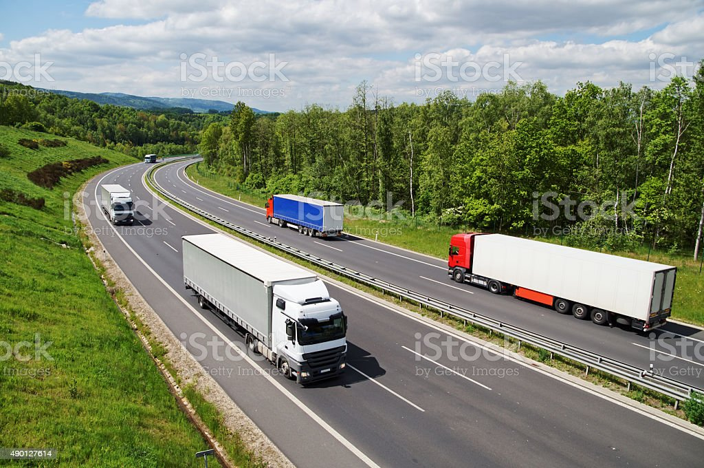Trucks traveling on an asphalt highway between forests. stock photo