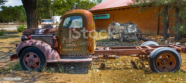 Taos, NM, USA-8 July 18: Two old trucks and  a farm wagon, setting outside the Red Arrow Emporium.