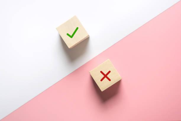 True and false symbols accept rejected for evaluation, Yes or No on wood blogs on pink and white background. True and false symbols accept rejected for evaluation, Yes or No on wood blogs on pink and white background. imitation stock pictures, royalty-free photos & images