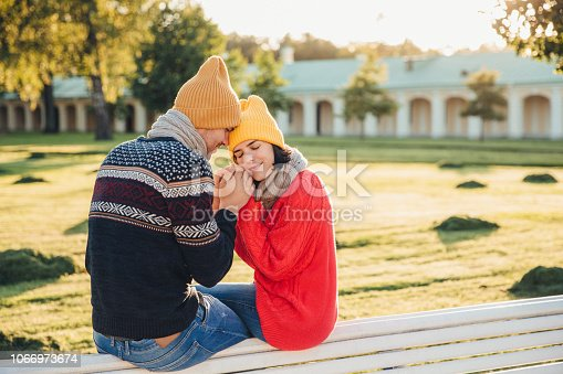 True feelings and romantisism concept. Adorable young woman in knitted yellow hat and red warm sweater warms her hands in boyfriend`s hands, sit together on bench, closes eyes with great enjoyment