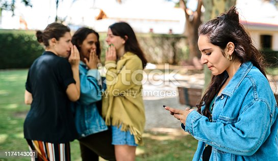 Cropped shot of a young attractive woman standing and using her cellphone while her classmates stand behind her and gossip