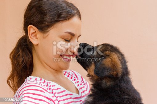 True friendship between girl and puppy who is giving a kiss.