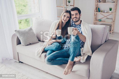 istock True love. Cheerful romantic couple is sitting on sofa under cozy plaid and smiling. They are drinking tea, wearing casual clothes, barefoot 939600690
