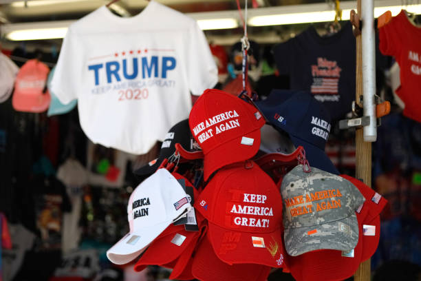 Trump MAGA hats and Reelection gear Washington, D.C., USA - July 21, 2019: A street vendor selling public domain Donald Trump paraphernalia and souvenirs. The souvenirs are located right across the street from the White House and taken on the afternoon of July 21, 2019 near Pennslyvania Avenue in Washington, D.C. The red hat is a signature symbol of his