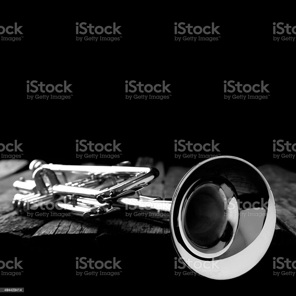 Trumpet on an old wooden table. Black and white. stock photo