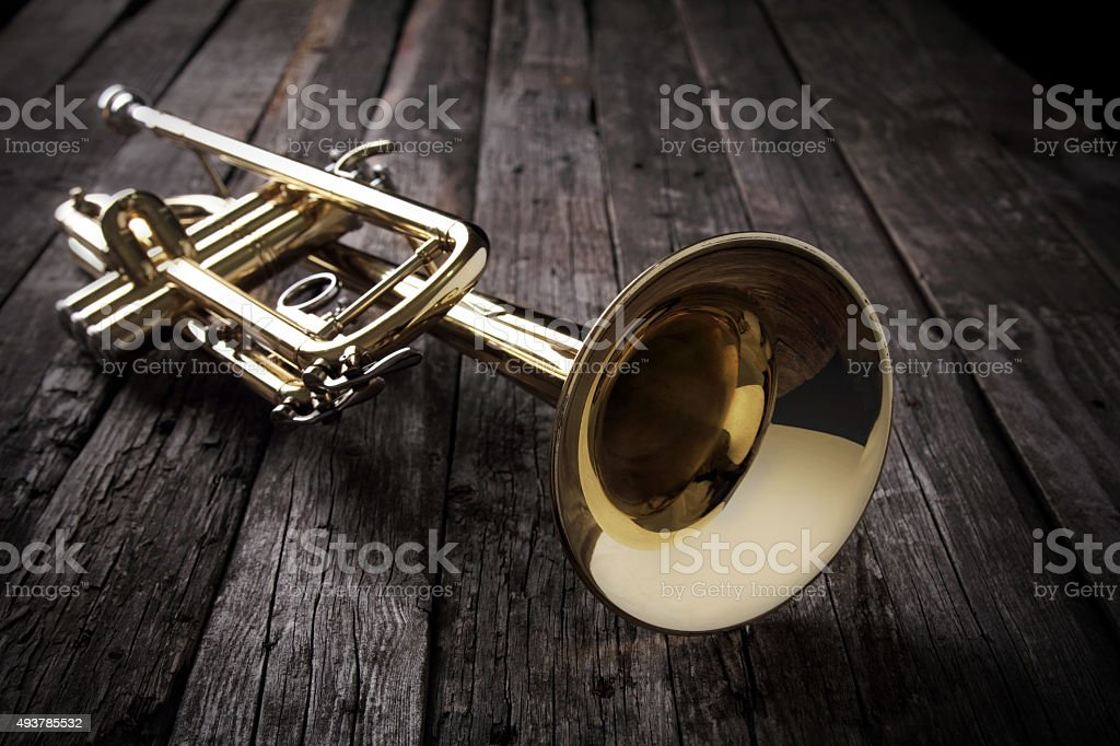 Trumpet on an old wooden table stock photo
