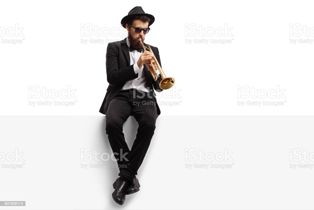 Trumpet player sitting on a panel stock photo