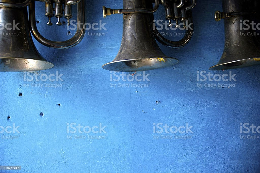 trumpets hanging on blue textured wall royalty-free stock photo