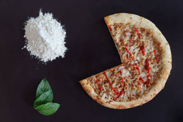 Truncated pizza, pile of flour and green leaves on black background stock photo