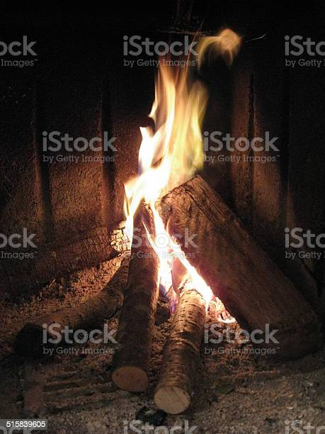 Photo of trunks of wood burn on red and yellow flame of fire