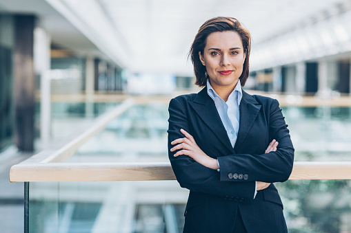 Young woman in business wear standing with armes crossed in business environment, with copy space.