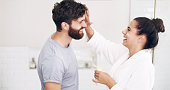 Shot of a happy young woman applying moisturiser on her husband's face during their morning grooming routine at home