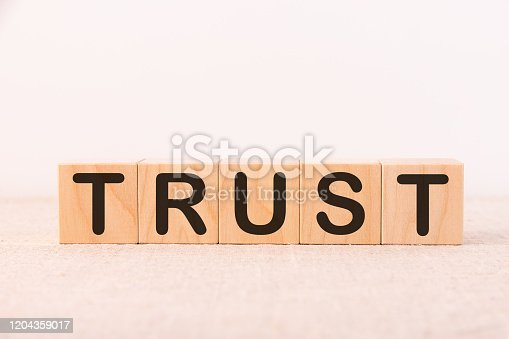939533958 istock photo Trust word concept written on wooden cubes on a light table and light background 1204359017