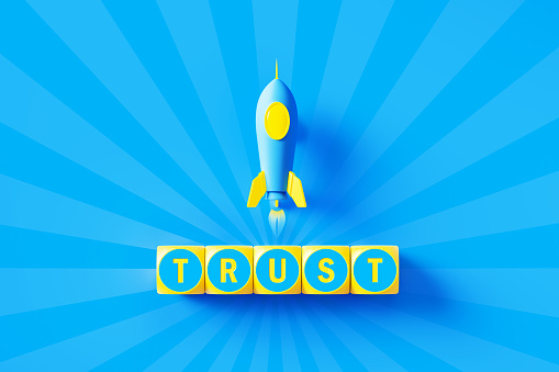 Trust written yellow wood blocks sitting below a blue rocket over blue starburst background. Horizontal composition with copy space. Trust concept.