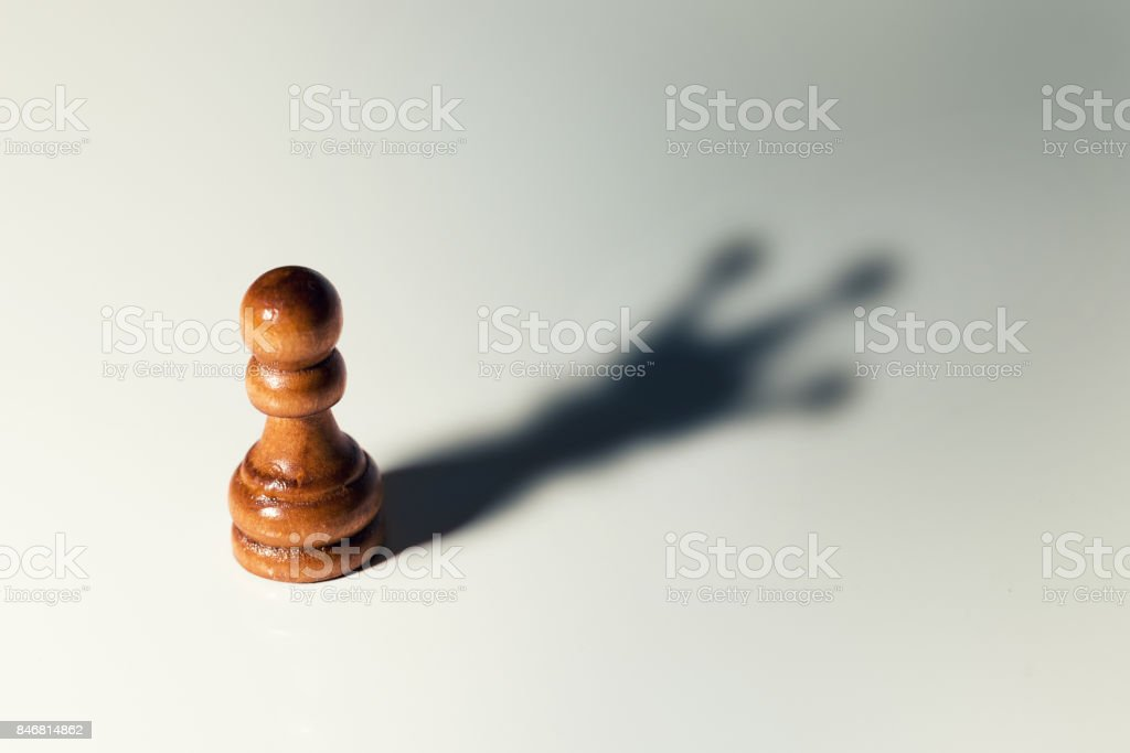 trust yourself concept - chess pawn with king shadow stock photo
