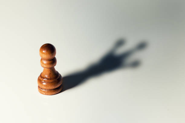 trust yourself concept - chess pawn with king shadow - bold stock photos and pictures