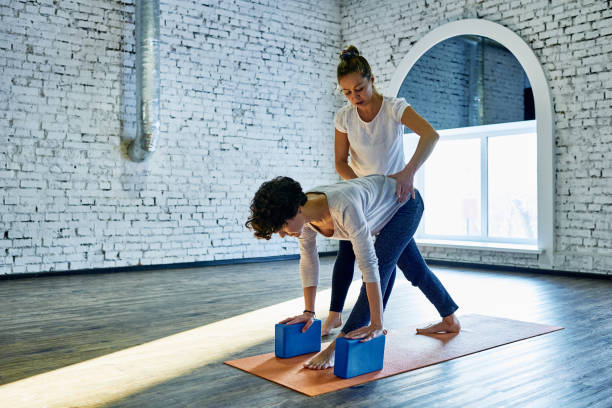 Trusting yoga trainer Skilled yoga coach pushing on lower back of student showing right posture of spine during exercising yoga instructor stock pictures, royalty-free photos & images