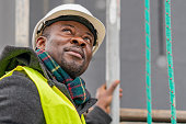 African American engineer wearing yellow protective workwear looking upwards among scaffolding