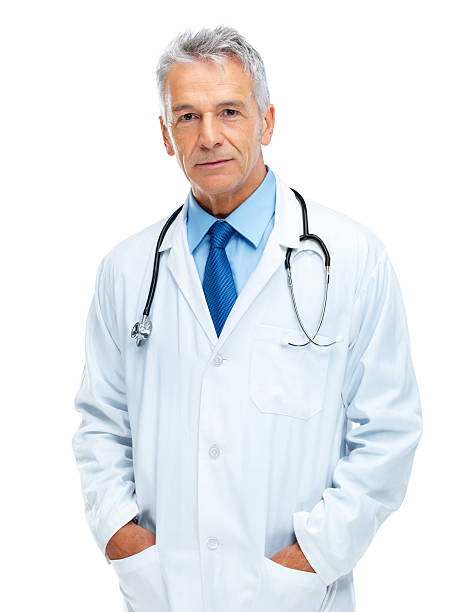 Trustworthy physician Portrait of confident senior medical doctor standing with hands in pockets isolated on white background hands in pockets stock pictures, royalty-free photos & images