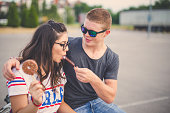 19 years old couple enjoy outdoors. They are eating ice cream after shopping