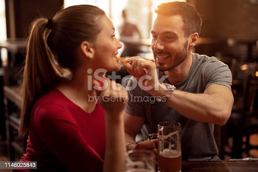 Happy man feeding his girlfriend with nacho chips while drinking beer together in a pub.