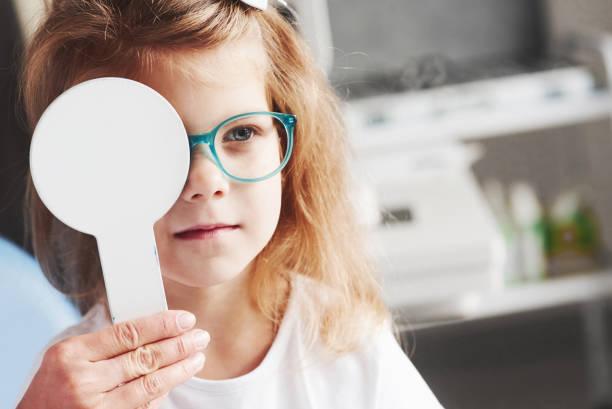 Versuchen Sie, dieses Wort zu lesen. Die Hände der Frau halten den Okkluder. Kleines Mädchen, das seine Vision mit einer neuen grünen Brille überprüft – Foto
