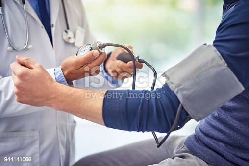 Shot of an unrecognizable male doctor checking the blood pressure of a patient while being seated inside of a hospital during the day