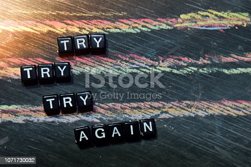 Try Try Try Again on wooden blocks. Cross processed image with blackboard background. Inspiration, education and motivation concepts