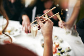 Cropped shot of an unrecognizable person eating with chopsticks during a dinner party