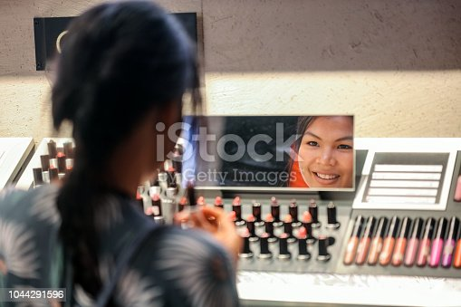Asian woman choosing lipstick in department store