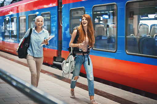 Closeup front side view of two women in a hurry as they disembarked one train and trying to catch their next ride on the track far to the their right. They are rushing and laughing at same time.