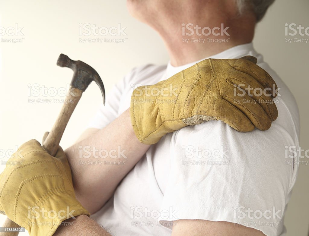 trying to do home maintenance with shoulder pain stock photo