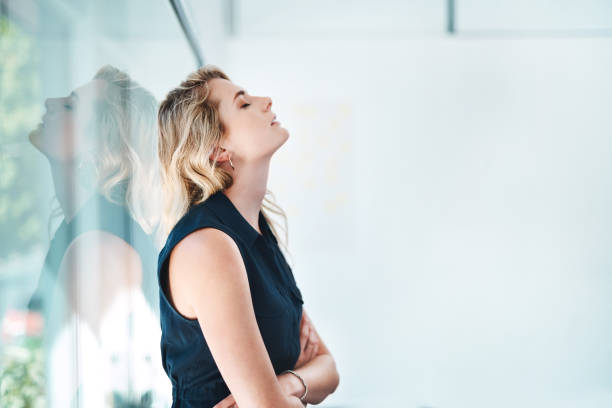 Trying to drag herself out of the doom and gloom Shot of a young businesswoman looking stressed out in an office mental burnout stock pictures, royalty-free photos & images