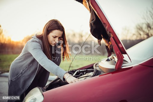 Woman on the road trying to fix the broken car, and calling for help on her mobile phone.