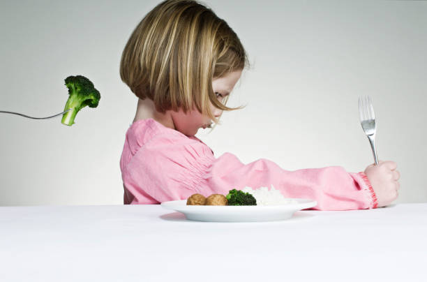 Trying To Get a Young Girl to Eat Her Greens stock photo