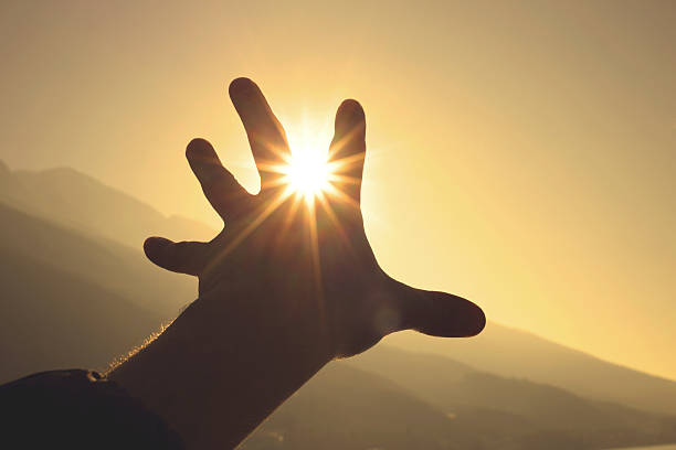 Trying to grab the sun with hand stock photo