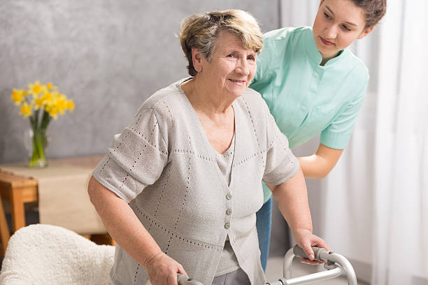 Trying to live normal despite disability Senior woman with walking stick and her helpful carer despite stock pictures, royalty-free photos & images
