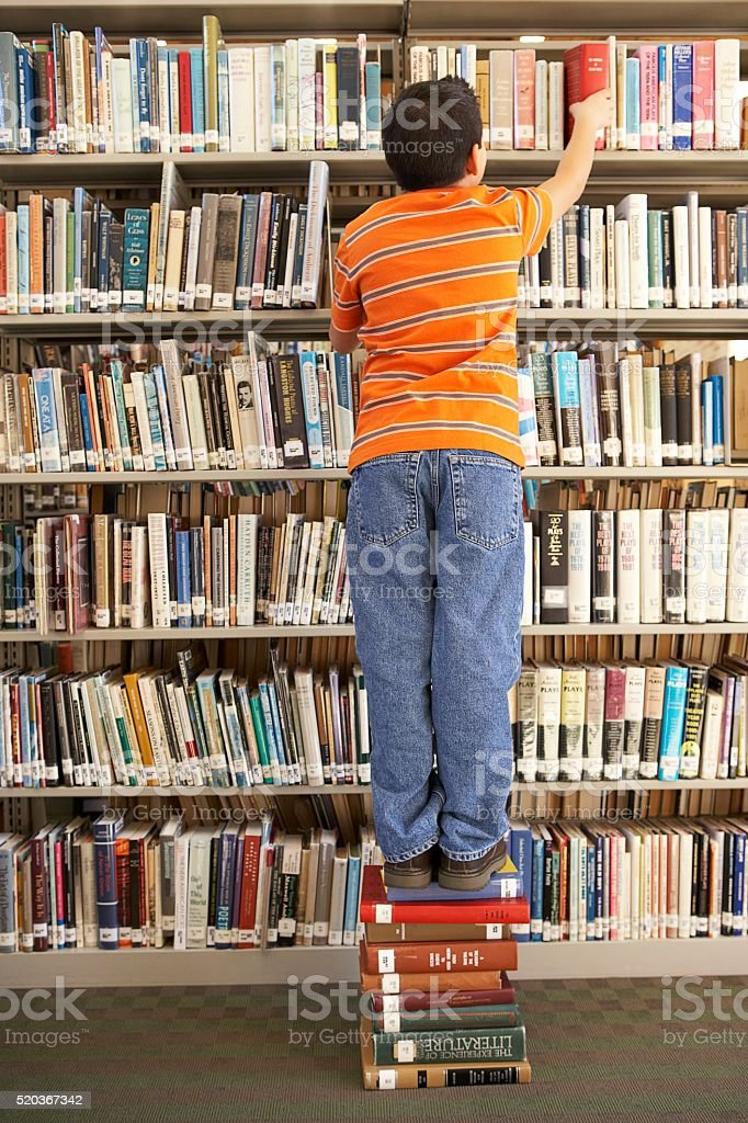 Trying to reach a book on the top shelf stock photo