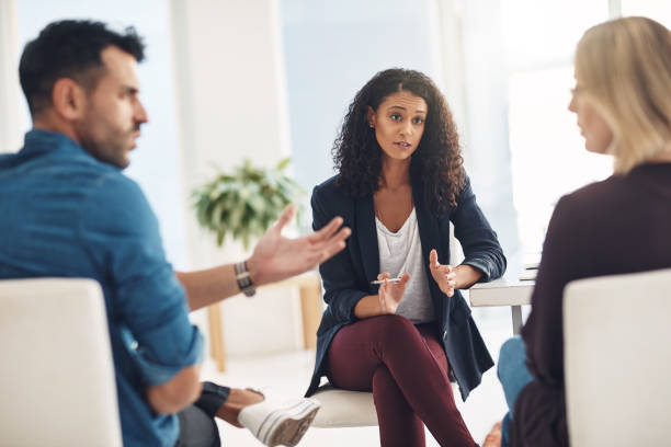 Trying to save a relationship Shot of a couple having an argument during a counseling session with a therapist conflict stock pictures, royalty-free photos & images