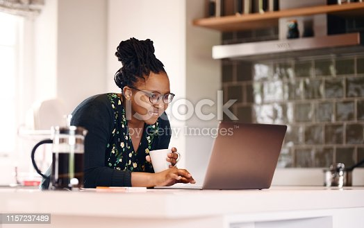 Shot of a young african american woman with a coffee cup using laptop in kitchen at home
