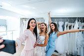 Young Caucasian beautiful women trying wedding dress helping her friend to choose wedding dress. Selfie time.
