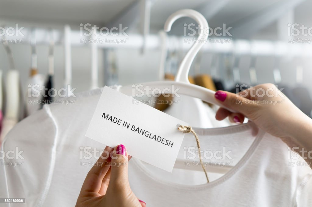 T-shirt made in Bangladesh. Customer looking at the origin and import country of a cheap fashion product in clothes store or shop. Ethical consumer behavior. Woman holding label and price tag with text. stock photo