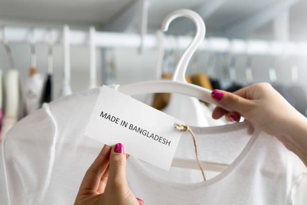 티셔츠는 방글라데시에서 만든입니다. 고객 옷 상점 또는 상점에서 저렴 한 패션 제품의 원산지와 수입 국가 보고. 윤리적 소비자 행동입니다. 레이블 및 텍스트와 가격표를 들고 여자입니다. 스톡 사진
